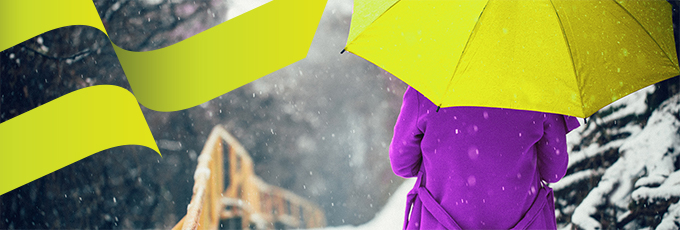 person walking in the snow with a purple coat and lime green umbrella
