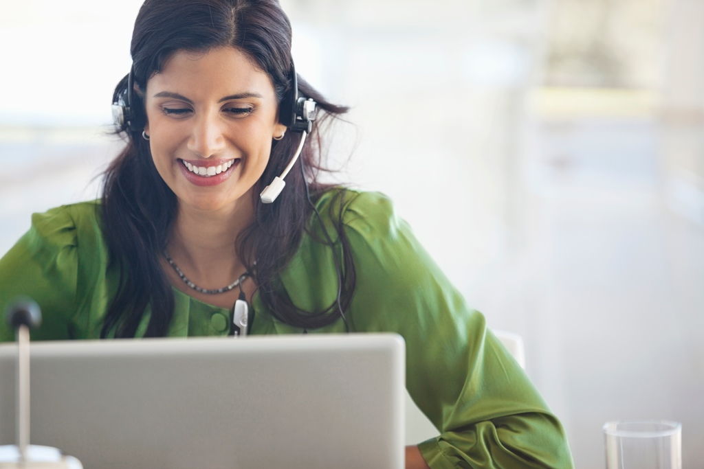 woman with headset smiling while looking at computer