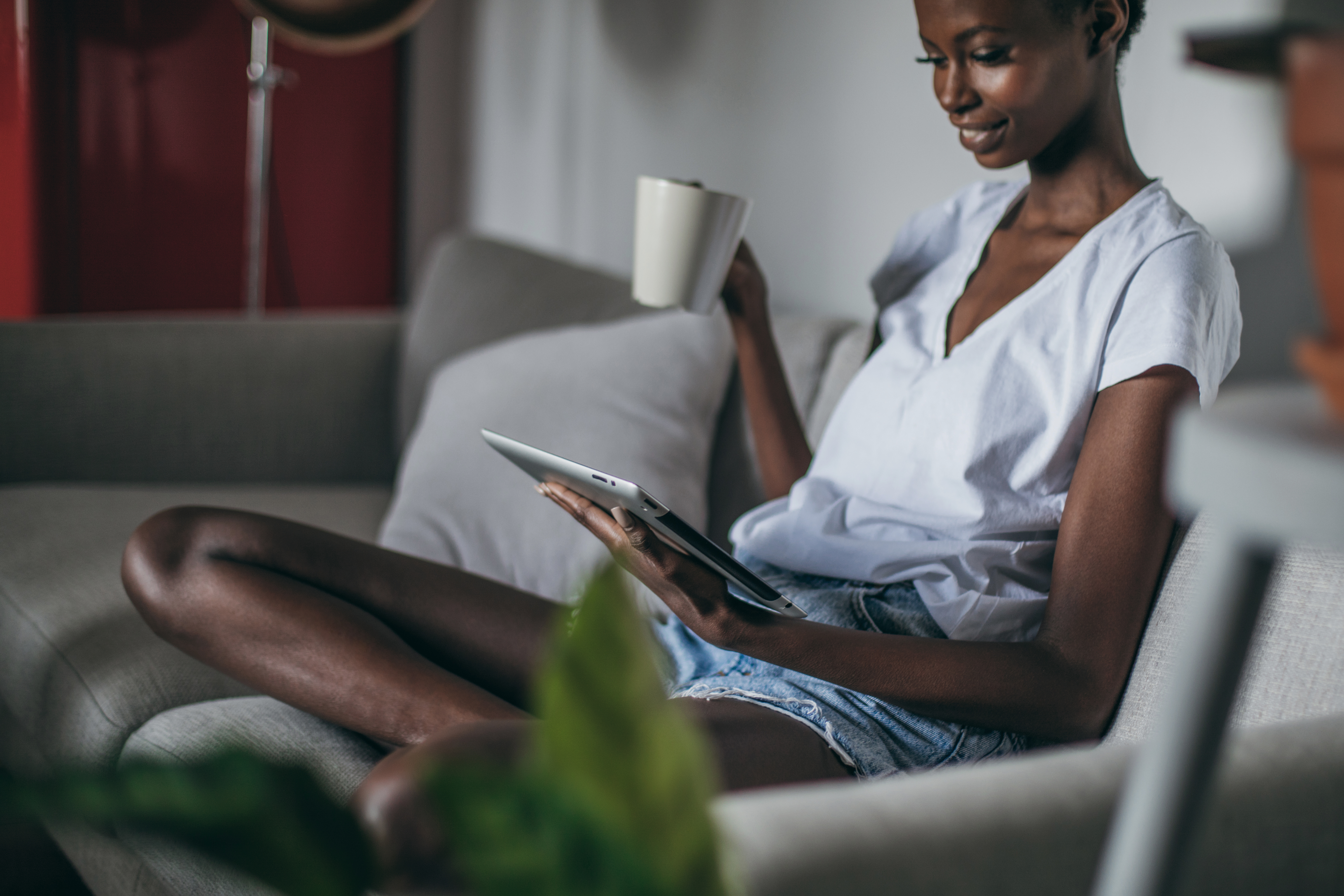 Woman sitting on the couch enjoying a coffee while looking at her electronic bill