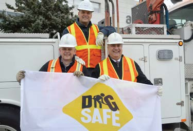 three workers holding up a dig safe flag